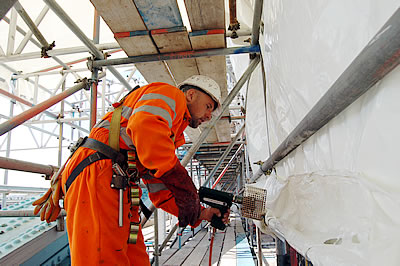 Envirowraps being heat boded to form a seamless enclosure around the scaffolding of the North East Suspension Chain of Tower Bridge