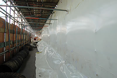 The hoarding (left) and the Envirowrap at ground level