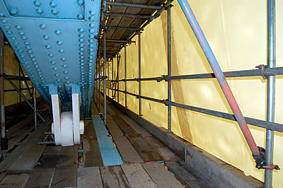 The long section of the South East Suspension Chain surrounded by scaffolding and Envirowrap