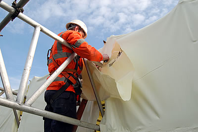 Envriowraps being applied to the scaffolding