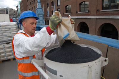 Grit being poured into the blast pot