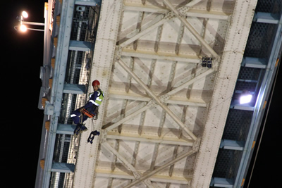 Abseiler fitting the clamps under the East Walkway