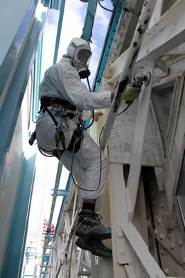 Abseiler removing the defective Top Coating