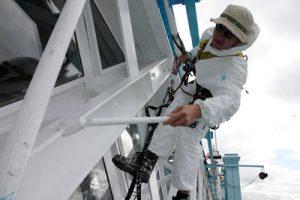 Abseiler applying the white finish coat