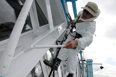 Abseiler applying the white finish coat